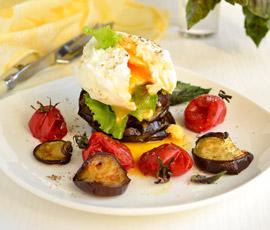 Huevo poché con daditos de gambas sobre lecho de verduras